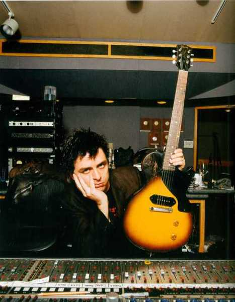Green Day's Billie Joe Armstrong poses with his Gibson Les Paul Special in the studio as he looks sullenly at the camera.