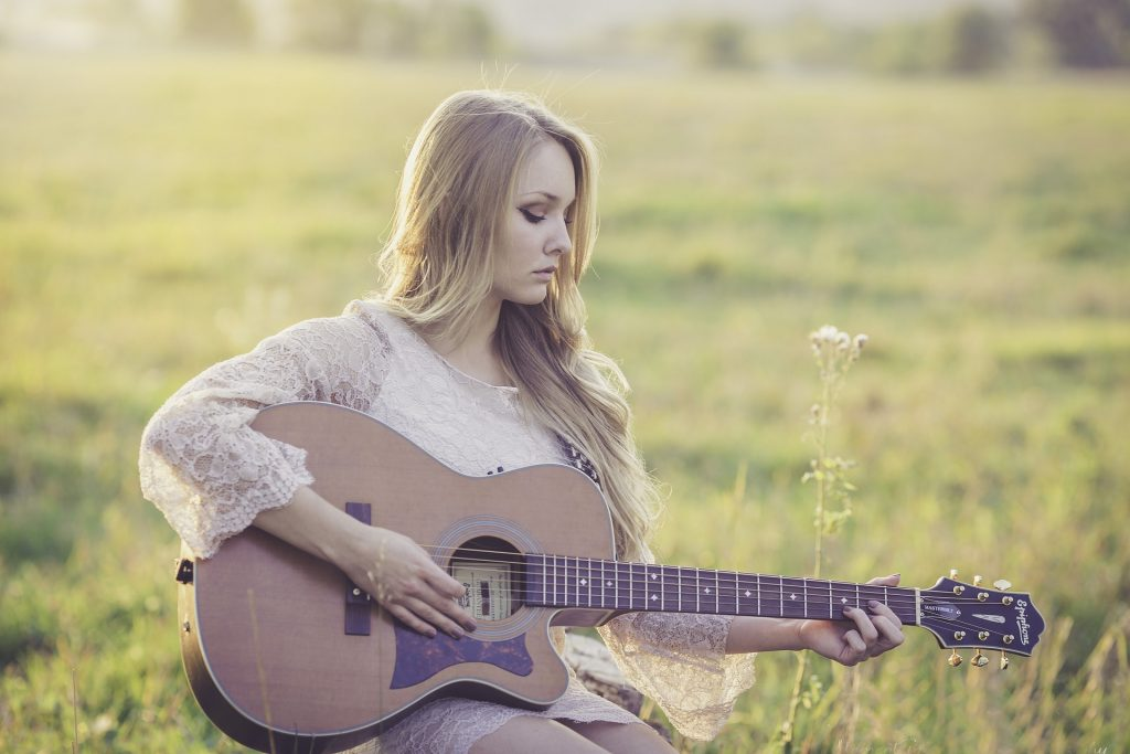 A woman sitting in a field while playing guitar