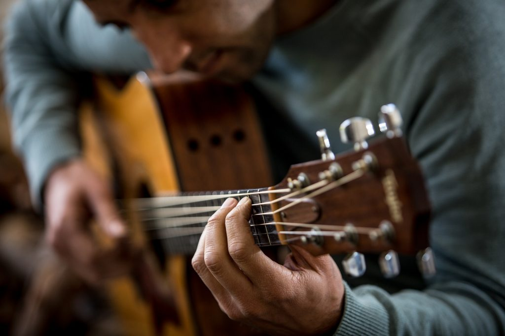 A man playing a g chord on guitar while sitting down
