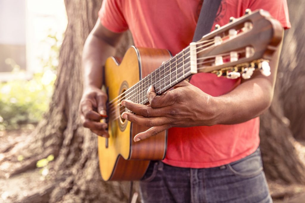A man playing guitar while standing