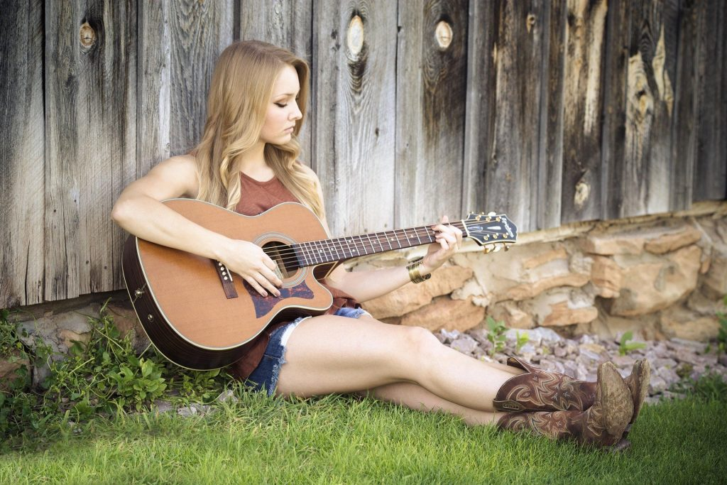 A woman in cowboy boots sitting in the grass while playing a g chord on guitar